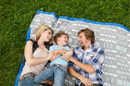 Happy family lying on blanket in meadow Stock Photo - Premium Royalty-Free, Code: 628-07072288