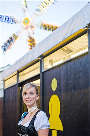 Woman standing in front of the women's restroom on the Oktoberfest in Munich, Bavaria, Germany Stock Photo - Premium Royalty-Free, Code: 628-07072375