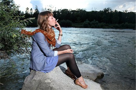 Young woman smoking a cigarette by the riverside Stock Photo - Premium Royalty-Free, Code: 628-07072449