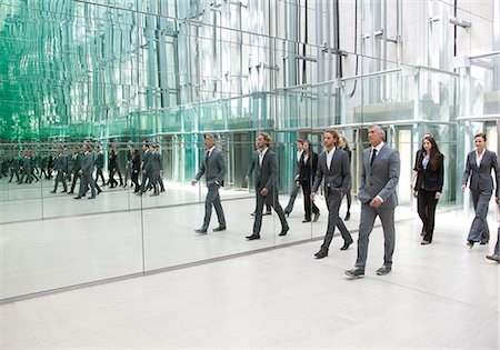Businesspeople walking along mirror wall Stock Photo - Premium Royalty-Free, Code: 628-07072538