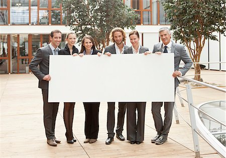 Group of businesspeople holding blank sign Stock Photo - Premium Royalty-Free, Code: 628-07072539
