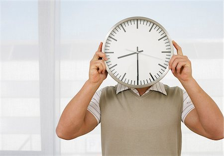 Man holding clock in front of his face Stock Photo - Premium Royalty-Free, Code: 628-07072547