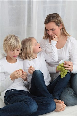 Mother and two children eating grapes on couch Stock Photo - Premium Royalty-Free, Code: 628-07072729