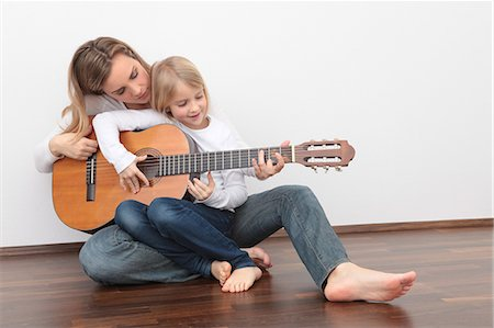 Daughter playing guitar on mother's lap Stock Photo - Premium Royalty-Free, Code: 628-07072734