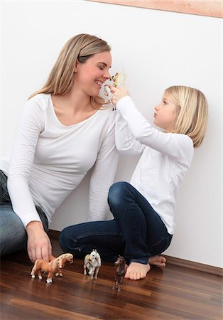 Mother and daughter playing with horse figures on the floor Stock Photo - Premium Royalty-Free, Code: 628-07072733