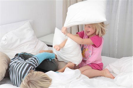 Brother and sister having a pillow fight in bed Stock Photo - Premium Royalty-Free, Code: 628-07072758