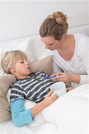 Mother taking the temperature of sick son in bed Stock Photo - Premium Royalty-Free, Code: 628-07072759