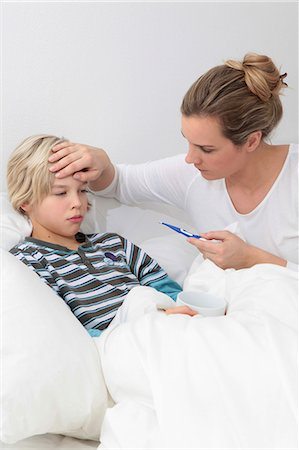 Mother taking the temperature of sick son in bed Stock Photo - Premium Royalty-Free, Code: 628-07072761