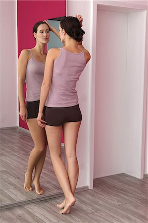 Brunette young woman in lingerie looking in mirror Stock Photo - Premium Royalty-Free, Code: 628-07072784