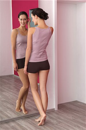 Brunette young woman in lingerie looking in mirror Stock Photo - Premium Royalty-Free, Code: 628-07072785