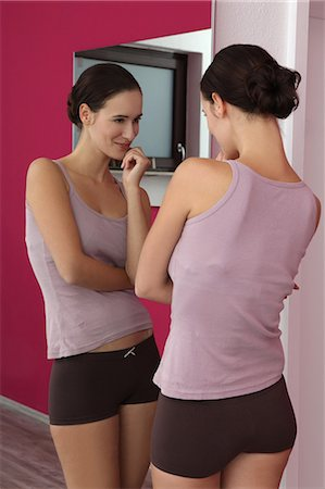 Brunette young woman in lingerie looking in mirror Stock Photo - Premium Royalty-Free, Code: 628-07072786