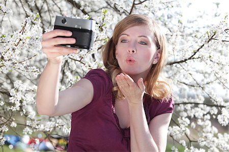 Woman taking picture of herself in front of blooming tree Stock Photo - Premium Royalty-Free, Code: 628-07072915