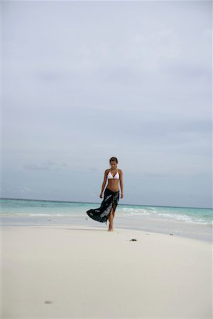 Young girl wearing bikini and pareo, walking along the beach Stock Photo - Premium Royalty-Free, Code: 628-00919174