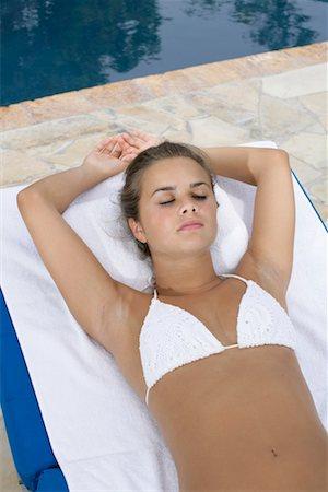 Young girl wearing bikini, lying on a towel at a swimming pool, sleeping Stock Photo - Premium Royalty-Free, Code: 628-00919173