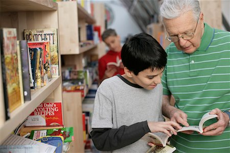 Grandfather and boy reading a book in front of a bookshelf, fully_released Stock Photo - Premium Royalty-Free, Code: 628-00919642
