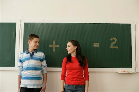 Two pupils standing in front of a blackboard, arithmetic problem in background Stock Photo - Premium Royalty-Free, Code: 628-00920590
