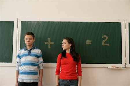 Two pupils standing in front of a blackboard, arithmetic problem in background Stock Photo - Premium Royalty-Free, Code: 628-00920628