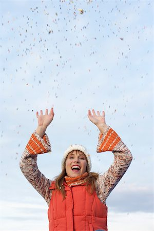 Young woman with scarf and cardigan under the sky while playing with confetti, close-up Stock Photo - Premium Royalty-Free, Code: 628-01278692