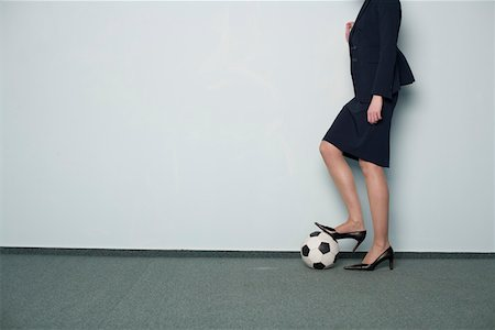 Businesswoman's foot on a soccer ball Stock Photo - Premium Royalty-Free, Code: 628-01639043