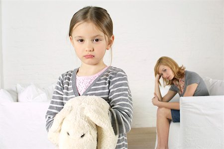 sad girls - Cheerless girl looking at camera, mother sitting in background Stock Photo - Premium Royalty-Free, Code: 628-02197920