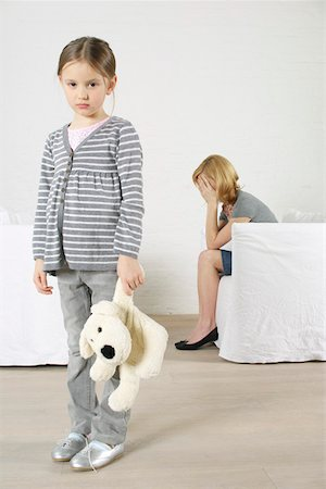 sad girls - Despaired woman sitting in armchair, girl holding stuffed animal standing in foreground Stock Photo - Premium Royalty-Free, Code: 628-02197958