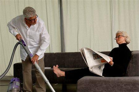 Senior man vacuuming, senior woman sitting on sofa while reading a newspaper Stock Photo - Premium Royalty-Free, Code: 628-02615210