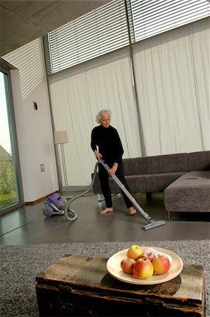 Senior woman vacuuming living room Stock Photo - Premium Royalty-Free, Code: 628-02615257