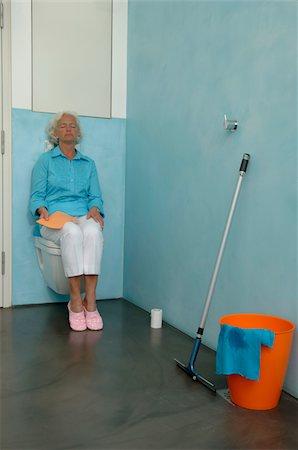 Exhausted senior woman sitting on toilet bowl Stock Photo - Premium Royalty-Free, Code: 628-02615250