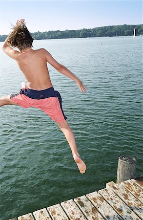 Boy jumping into Water from a wooden Footbridge - Salutation - Fun - Summer - Swimming Stock Photo - Premium Royalty-Free, Code: 628-02615685