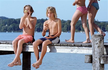 Two Boys with naked Torso eating Bread while two Girls in Bikini walk by - Snack - Leisure Time - Friendship - Lake Stock Photo - Premium Royalty-Free, Code: 628-02615705
