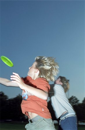 Two Boys trying to catch a Frisbee out of the Air - Game - Leisure Time - Youth - Park - Twilight Stock Photo - Premium Royalty-Free, Code: 628-02615726
