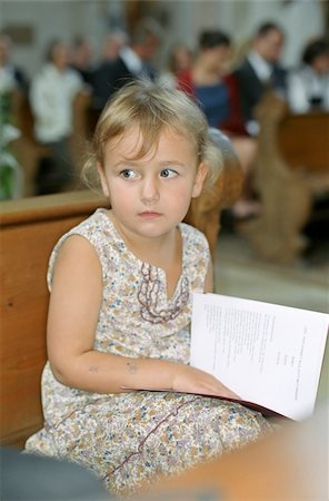 Little Girl with a Songbook in her Lap sitting on a Bench in a Church - Ceremony - Baptism - Christianity - Childhood Stock Photo - Premium Royalty-Free, Code: 628-02615785