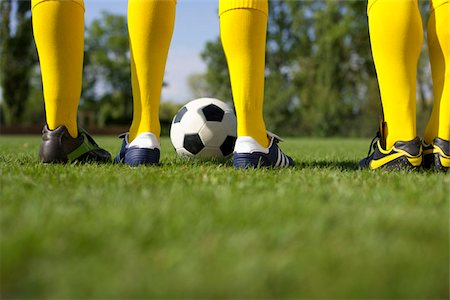 Three soccer players standing side by side Stock Photo - Premium Royalty-Free, Code: 628-02954216