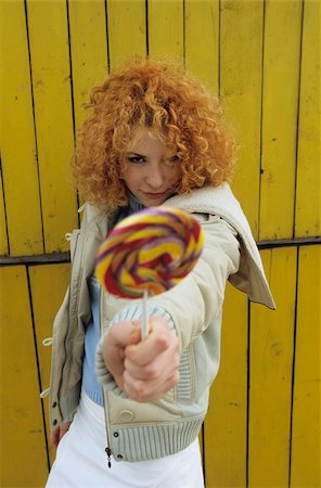 Young redhaired Woman elongating a Lollipop in the Face of the Spectator - Facial Expression - Allurement - Sweets Stock Photo - Premium Royalty-Free, Code: 628-02954670