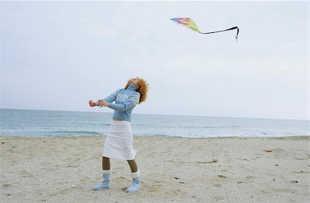 Young Woman with red Curls holding a Kite on a String - Leisure Time - Fun - Beach - Season Stock Photo - Premium Royalty-Free, Code: 628-02954671