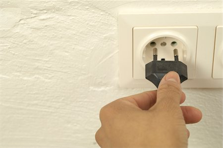 Woman putting plug into electrical outlet Stock Photo - Premium Royalty-Free, Code: 628-02953518