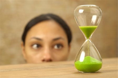 sand clock - Woman looking at hourglass with green sand Stock Photo - Premium Royalty-Free, Code: 628-02953551