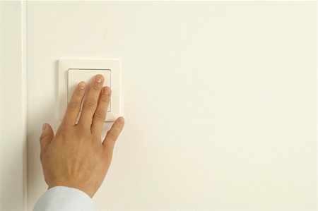 Woman pressing light switch Stock Photo - Premium Royalty-Free, Code: 628-02953578