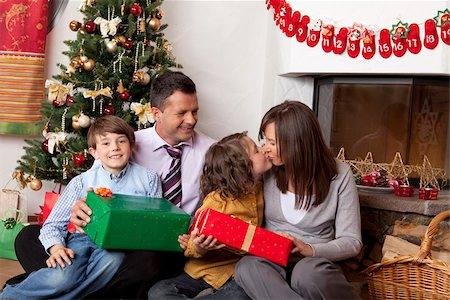 preteen kissing - Family with two children at Christmas tree Stock Photo - Premium Royalty-Free, Code: 628-02953679