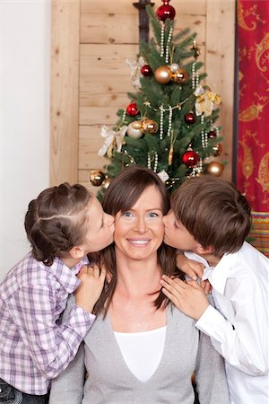 preteen kissing - Boy and girl kissing their mother at Christmas tree Stock Photo - Premium Royalty-Free, Code: 628-02953692