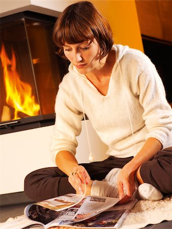 sweater and fireplace - Young woman reading magazine by the fireside Stock Photo - Premium Royalty-Free, Code: 628-02953795