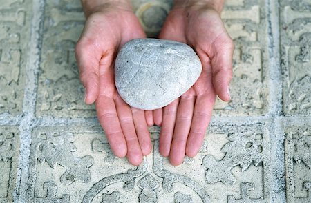 element - Woman holding a Stone over an ornate Ground - Meditation - Element Stock Photo - Premium Royalty-Free, Code: 628-02953982