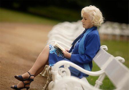 Senior woman reading book on park bench Stock Photo - Premium Royalty-Free, Code: 628-03058867
