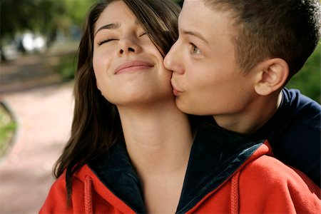 Teenage couple embracing while he kissing her Stock Photo - Premium Royalty-Free, Code: 628-03201433