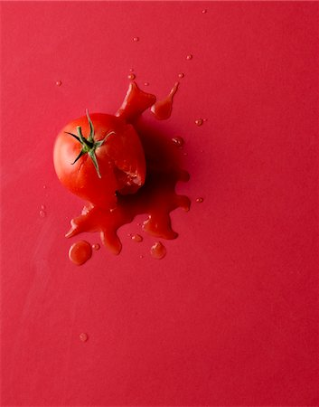 Smashed tomato on red background. Stock Photo - Premium Royalty-Free, Code: 621-05787101