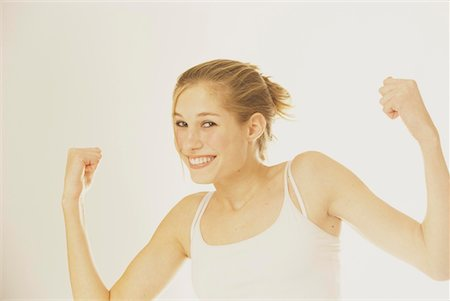 Portrait of Young Blonde Teenager Flexing Muscles Stock Photo - Premium Royalty-Free, Code: 621-00687581
