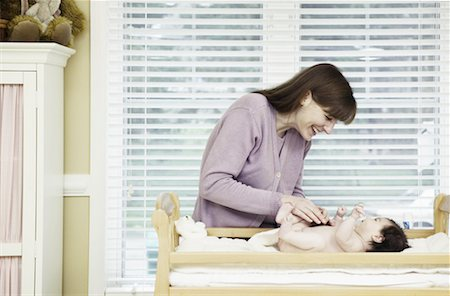 Playful Mother Changing Baby's Diaper Stock Photo - Premium Royalty-Free, Code: 621-00745464