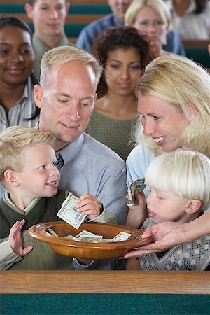Family in Church Putting Money in Offering Plate Stock Photo - Premium Royalty-Free, Code: 621-00795275