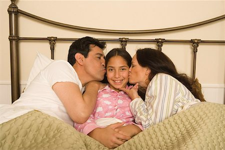 preteen kissing - Family in bed with daughter Stock Photo - Premium Royalty-Free, Code: 621-00994789