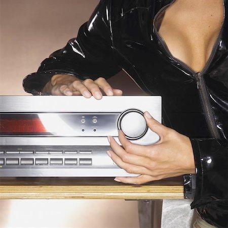 Woman in Shiny Black Bondage Gear Turning Up Volume Stock Photo - Premium Royalty-Free, Code: 621-01004497
